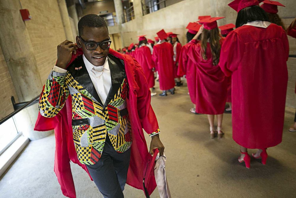 Benjamin Kalala walks up the ramp to his spot in line wearing a custom sport coat made by his mother before the Springfield High School graduation at the Bank of Springfield Center Saturday June 3, 2017 [Photo by Jason Johnson]