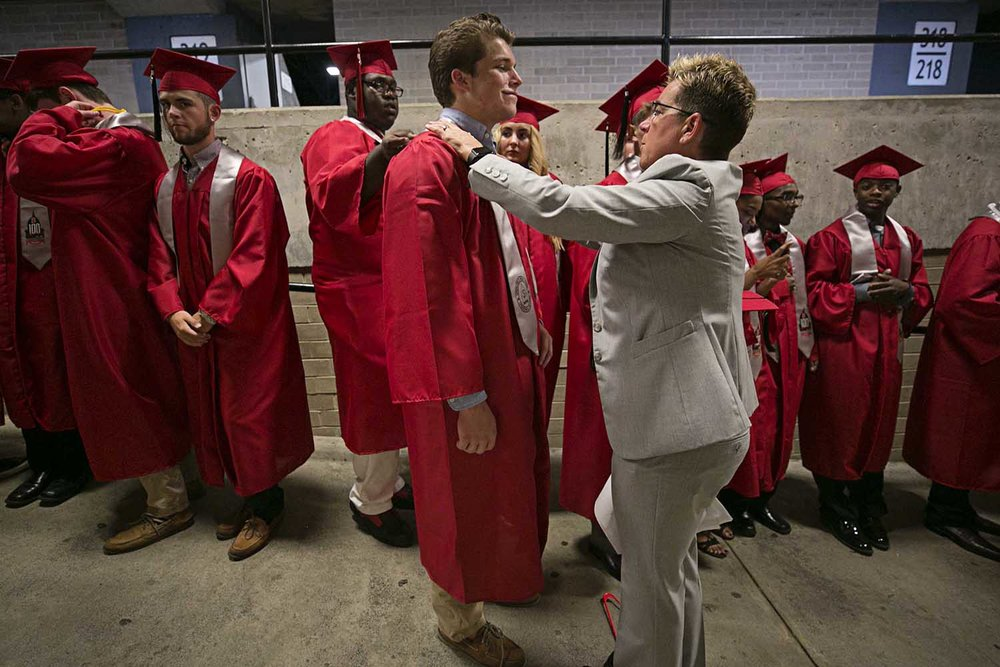 Mason Fitch gets some last minute help from assistant principal Lori Smith before the Springfield High School graduation at the Bank of Springfield Center Saturday June 3, 2017 [Photo by Jason Johnson]