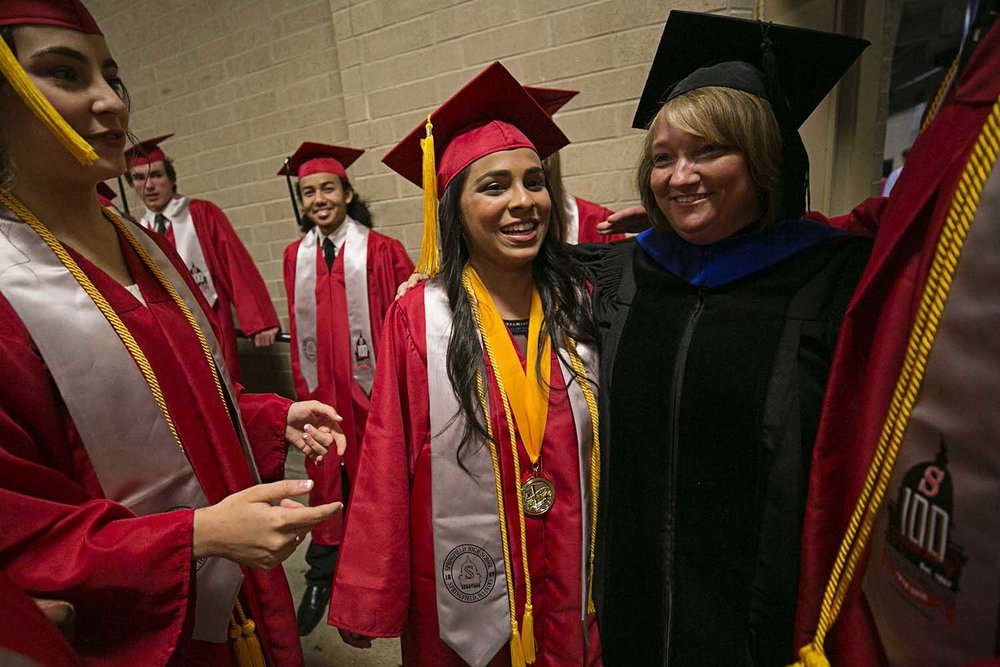 Valedictorian Alina Sinha embraces Superintendent of District 186 Jennifer Gill before the Springfield High School graduation at the Bank of Springfield Center Saturday June 3, 2017 [Photo by Jason Johnson]
