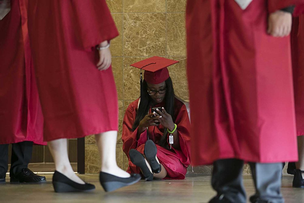 Chime Udaku sits and waits for the procession to line up before the Springfield High School graduation at the Bank of Springfield Center Saturday June 3, 2017 [Photo by Jason Johnson]