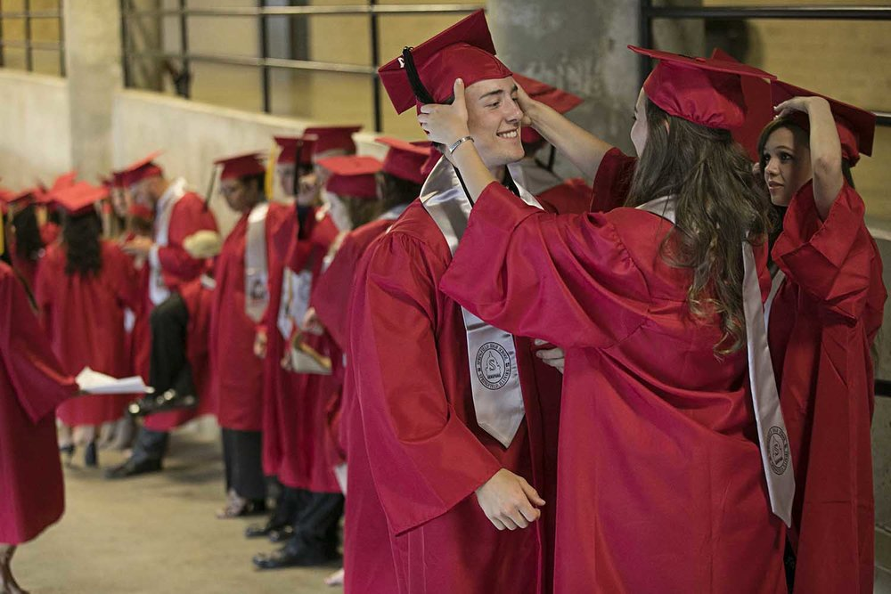 Corbin Tidall gets some help with his mortarboard from classmate Benedetta Sarti before the Springfield High School graduation at the Bank of Springfield Center Saturday June 3, 2017 [Photo by Jason Johnson]