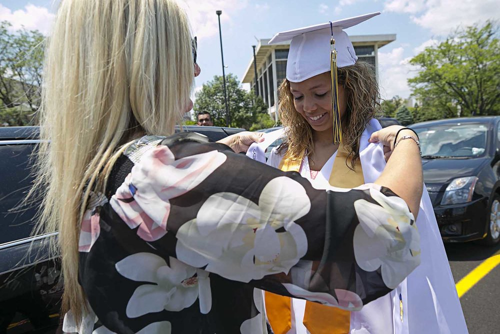 Melissa Edie helps daughter Ivy Greer put on her robe before the Springfield Southeast High School graduation at the Bank of Springfield Center Saturday June 3, 2017 [Photo by Jason Johnson]
