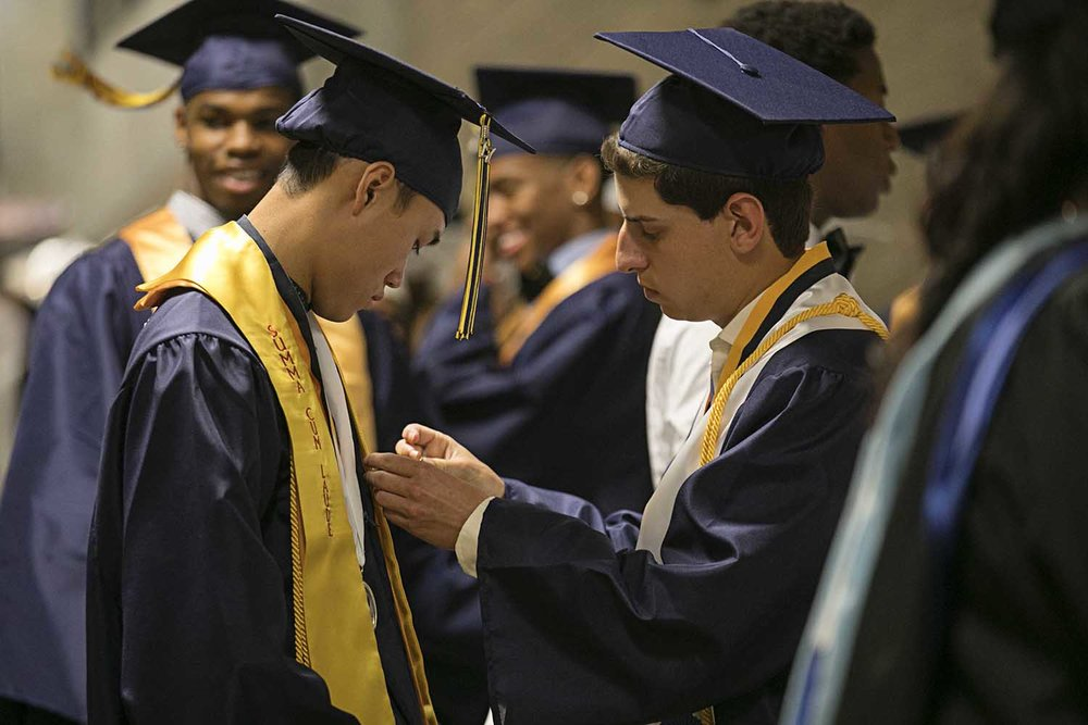 Matthew Bloomberg at right helps Salutatorian Kien Ho with a pin on his robe before the Springfield Southeast High School graduation at the Bank of Springfield Center Saturday June 3, 2017 [Photo by Jason Johnson]