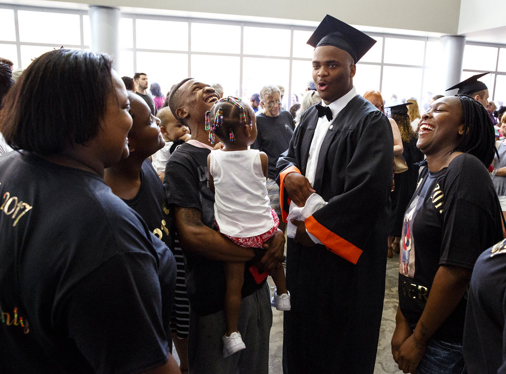 Jacob Whitfield is greeted by family after graduating from Lanphier High School at the Bank of Springfield Center Saturday, June 3, 2017. From left are his mother, Shayla Whitfield; sister, Ainjell; cousin Terrell Brown and his daughter, Harmony and  sister, Vasean O'Neal. [Rich Saal/The State Journal-Register]