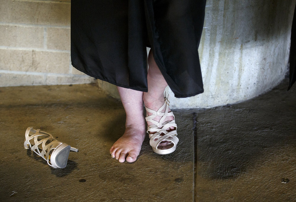 Things hadn't even started yet but Lillian Sears had decided that her new shoes were uncomfortable at the Lanphier High School graduation at the Bank of Springfield Center Saturday, June 3, 2017. [Rich Saal/The State Journal-Register]