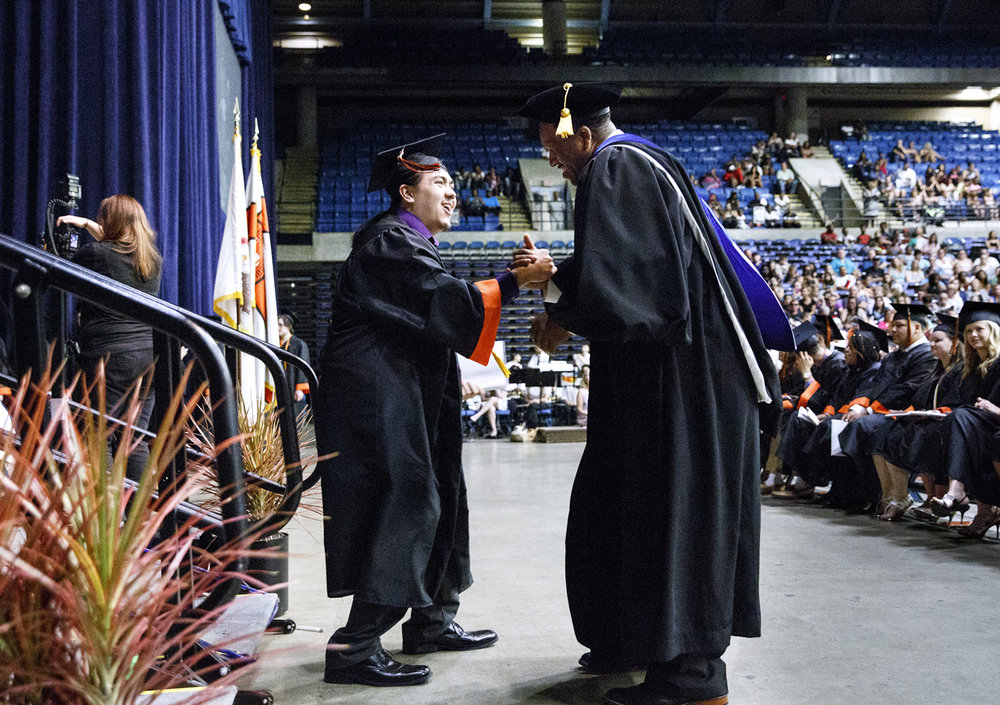 Lanphier High School principal Artie Doss greets Ethan McQuillan, as well as every one of the graduates, after they received their diploma at Lanphier's graduation at the Bank of Springfield Center Saturday, June 3, 2017. [Rich Saal/The State Journal-Register]