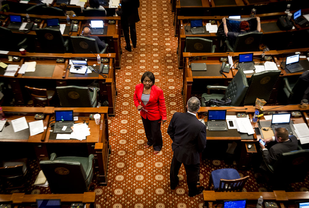 Illinois State Rep. Mary Flowers, D-Chicago, center, crosses the aisle to speak with Illinois State Rep. David Harris, R-Arlington Heights, during debate on SB 1722, a bill that would lengthen the prison sentence for repeat gun offenders, on the floor of the Illinois House at the Illinois State Capitol, Monday, May 29, 2017, in Springfield, Ill. [Justin L. Fowler/The State Journal-Register]