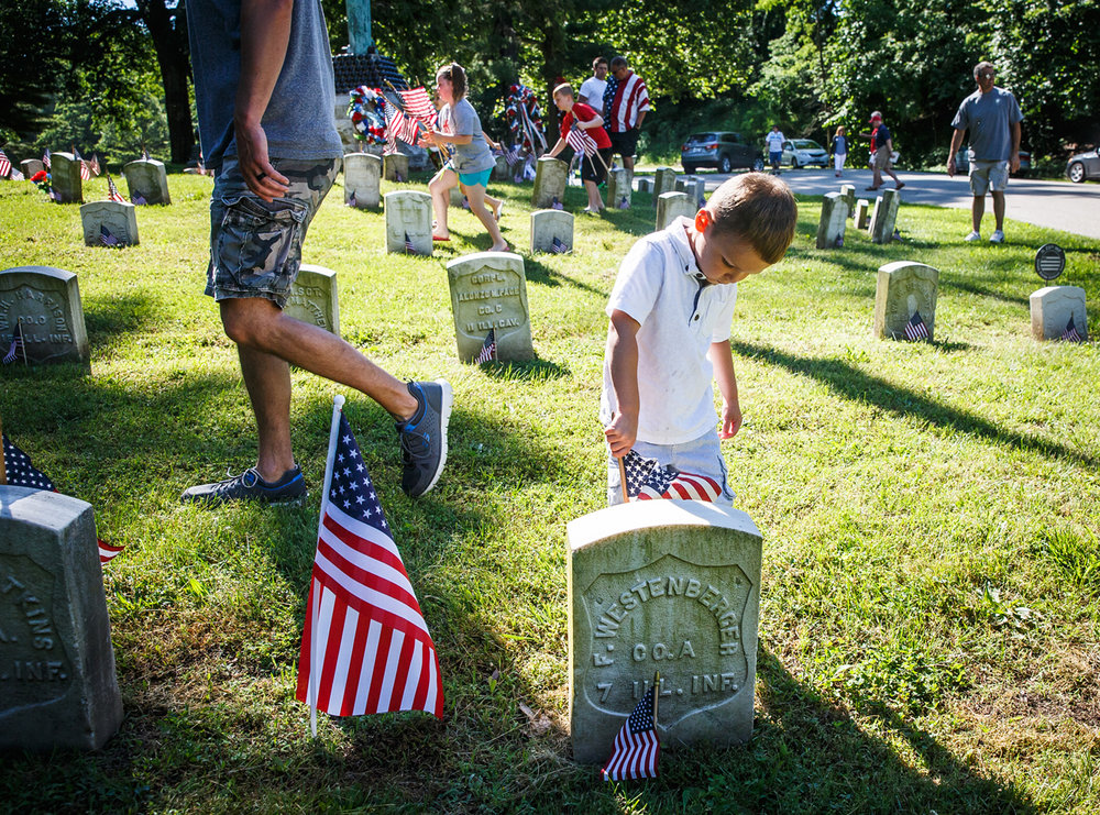 Bentley Weiss, 2, of Chatham, Ill., helps to remove the flags from the 97 gravestones at the Grand Army of the Republic Mound after the Interveterans Council of Sangamon County Memorial Day ceremony, Monday, May 29, 2017, in Springfield, Ill. The site was for Union Army Veterans who did not have family plots elsewhere and the first was in 1891 and the last was in 1930. [Justin L. Fowler/The State Journal-Register]