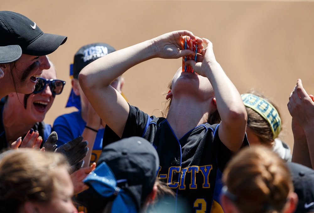 Tri-City's Ashlyn Sturdy (3) downs a heavy serving of powdered candy during a pre-game ritual with the team as they get set to take on St. Joseph Ogden during the Class 2A Athens Supersectional at Athens High School, Monday, May 29, 2017, in Athens, Ill. [Justin L. Fowler/The State Journal-Register]