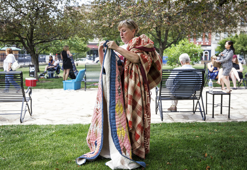 """Linda Renehan, owner of Springfield Vintage, packs up the blankets that were free to borrow for anyone on the lawn of the Old State Capitol for """"Lunch On The Lawn"""" during the Artist on the Plaza series on the Old State Capitol Plaza, Thursday, June 1, 2017, in Springfield, Ill. Springfield Vintage will be providing blankets each Thursday for patrons to use while enjoying the Artist on the Plaza series or having lunch through the summer. [Justin L. Fowler/The State Journal-Register]"""