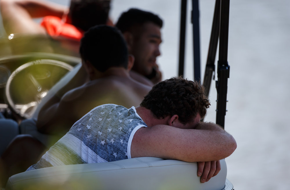 Young men on a pontoon react as a emergency personnel look for a person that went into the water from the boat into Lake Springfield, but never resurfaced near the shoreline of Lincoln Memorial Garden, Friday, June 2, 2017, in Springfield, Ill. [Justin L. Fowler/The State Journal-Register]