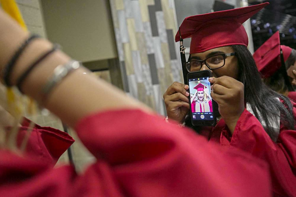 Jailynn Brown holds a phone for Jenna Milward as she gets her mortarboard straight before the Springfield High School graduation at the Bank of Springfield Center Saturday June 3, 2017. [Photo by Jason Johnson]