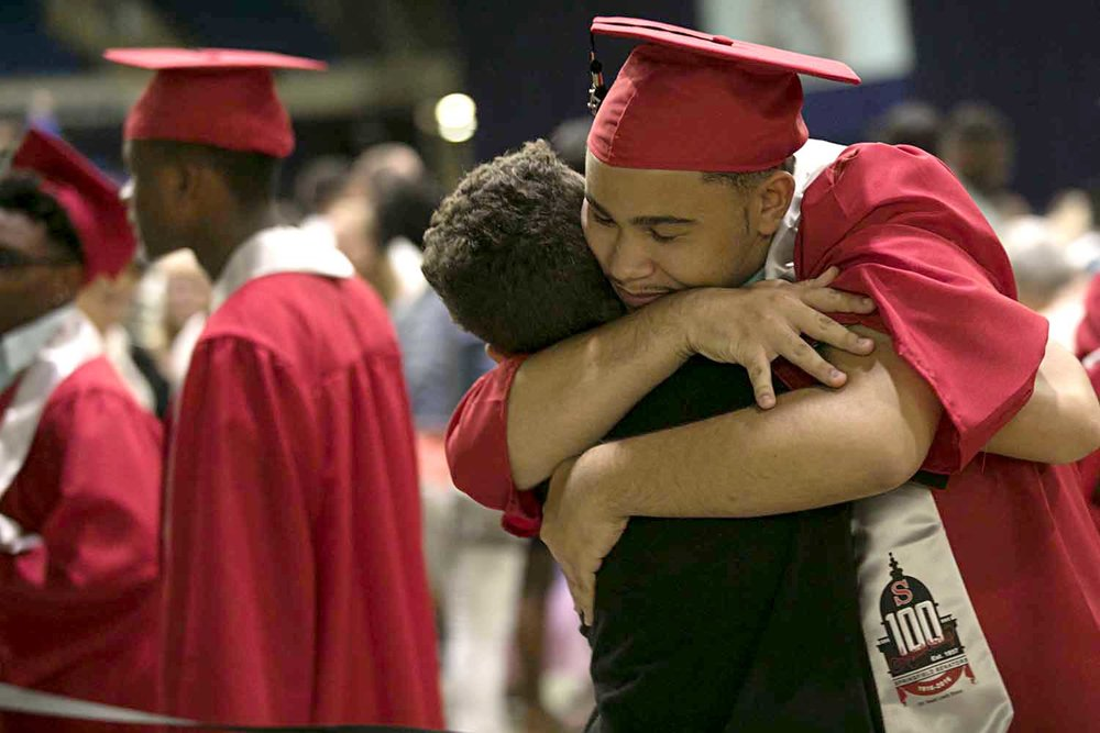 Elijah Phillips embraces little brother, Noah, before the Springfield High School graduation at the Bank of Springfield Center Saturday June 3, 2017. [Photo by Jason Johnson]