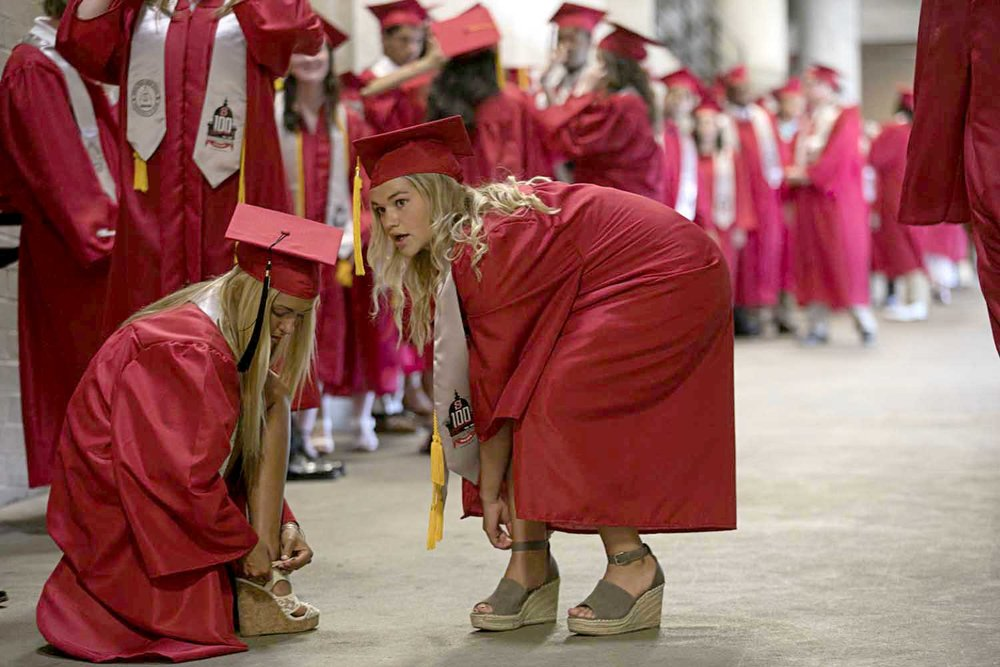 Camryn Milling, left, and Jenna Milward fix the heels on their shoes before the Springfield High School graduation at the Bank of Springfield Center Saturday June 3, 2017. [Photo by Jason Johnson]