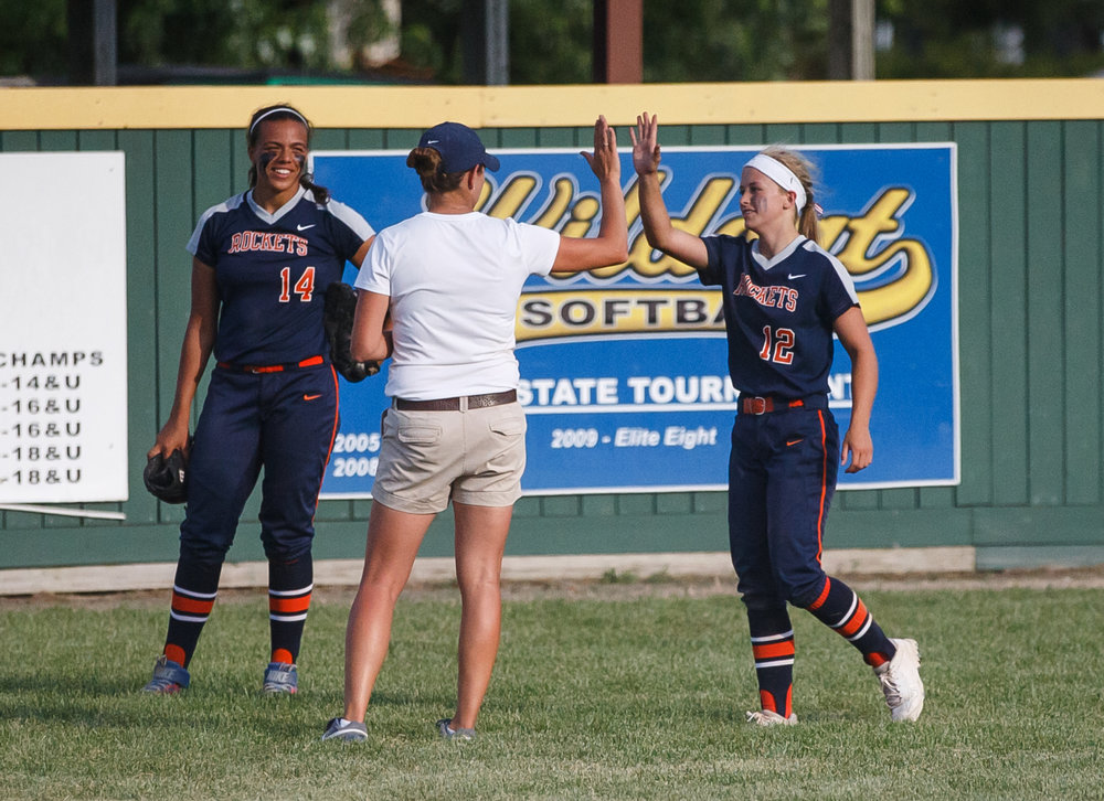 Rochester's Jillian Anderson (12) gets a high five from Rochester softball head coach Lindsay Howard after getting checked out from a collision with Rochester's Lyric Boone (14) in the outfield in the seventh inning against Herrin during the Class 3A Mattoon Supersectional at the Roundhouse Sports Complex, Monday, June 5, 2017, in Mattoon, Ill. [Justin L. Fowler/The State Journal-Register]