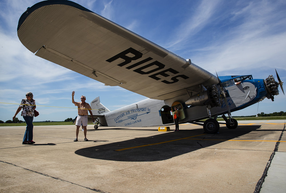 Guests stop and wave before boarding the Experimental Aircraft Association's Ford Tri-Motor NC8407 before a flight at the Jacksonville Municipal Airport Thursday, June 8, 2017. [Ted Schurter/The State Journal-Register]