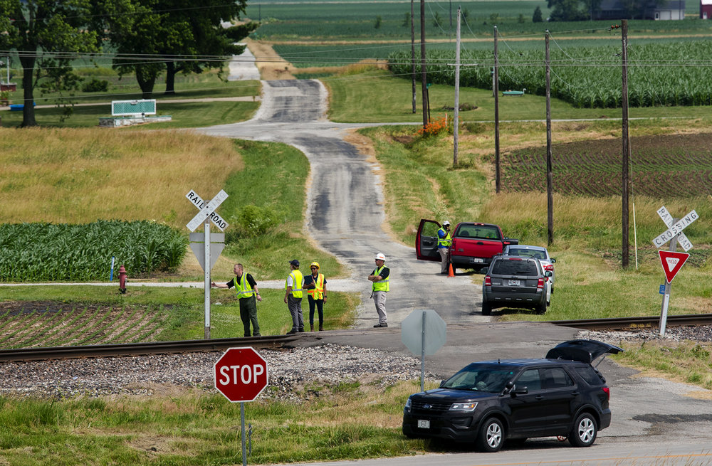 An Illinois State Police Traffic Crash Reconstruction Officer, left, checks a railroad crossing sign at the scene of an accident Wednesday between a van and a freight train that killed five elderly Pana residents. The van was southbound on County Road 1800 North, just north of Illinois 16, at 6:49 p.m. when the collision occurred with a westbound Union Pacific freight train. [Ted Schurter/The State Journal-Register]