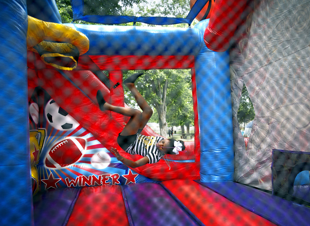 Nakala Washington flips inside a bounce house at Springfield's annual Juneteenth Celebration Saturday, June 17, 2017 at Comer Cox Park. [Rich Saal/The State Journal-Register]