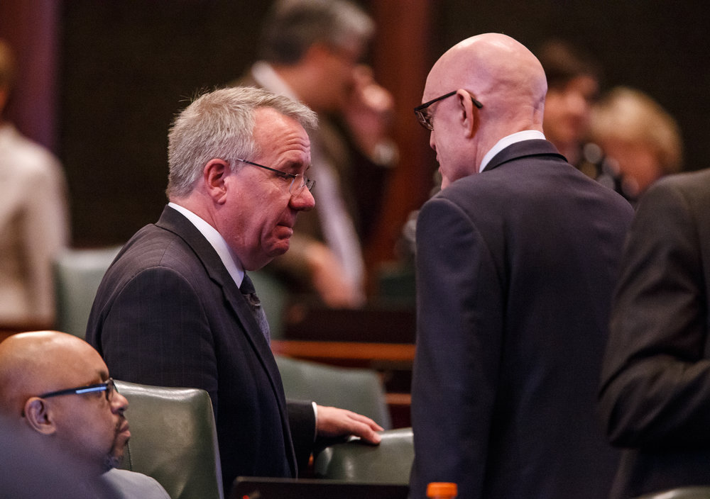 Illinois State Rep. Steve Andersson, R-Geneva, left, talks with Illinois State Rep. Greg Harris, D-Chicago, right, on the floor of the Illinois House as members gather for a vote on the tax hike bill during the overtime session at the Illinois State Capitol, Sunday, July 2, 2017, in Springfield, Ill. [Justin L. Fowler/The State Journal-Register]