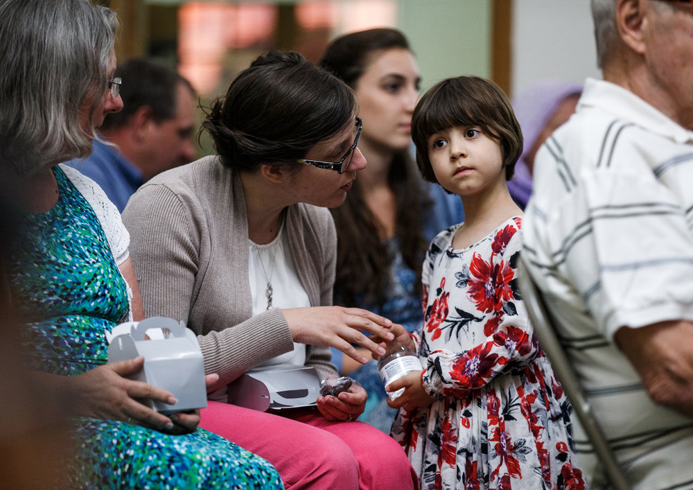 Hazel Calderon, 4, prepares to break the fast with water and a date along with her mother Rianne Hawkins, left, and members of the Islamic Society of Greater Springfield during an open house during the Muslim holy month of fasting, known as Ramadan, Sunday, June 18, 2017, in Springfield, Ill. Calderon asked her mother to attend after learning about learning about Ramadan. [Justin L. Fowler/The State Journal-Register]