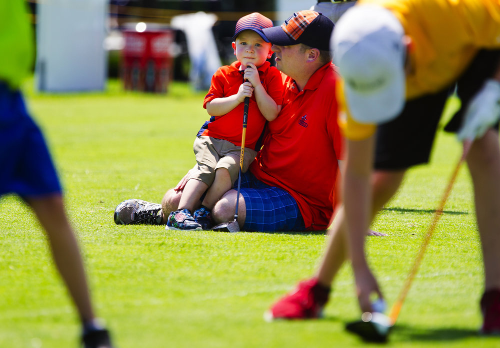 Three-year-old Gavin Jeffers leans on his dad Chris as he watches the older boys tee up a few shots during the Lincoln Land Charity Championship PGA GATEWAY Section Junior Clinic at Panther Creek Tuesday, June 20, 2017. According to his dad, Gavin plays putt putt golf and practices on the driving range. [Ted Schurter/The State Journal-Register]