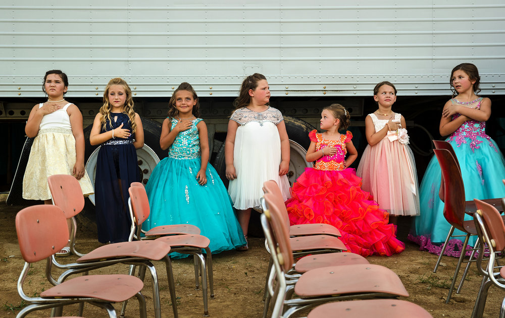 Little Miss candidates line up backstage and listen to the National Anthem during the Queen Pageant at the 32nd Annual Montgomery County Fair in Butler, Ill. Wednesday, June 21, 2017. The fair continues through Sunday, July 25. [Ted Schurter/The State Journal-Register]