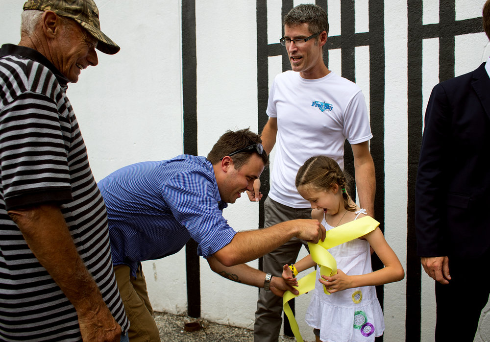 "Brandon Turley ties a yellow ribbon around Troy Freeman's daughter, Ginnie, moments after it was cut during the dedication the newest downtown mural, ""PraireSumac,"" on a building at Fifth and Monroe streets Thursday, June 22, 2017. Freeman, owner of Free Sky Studios, painted a Frank Lloyd Wright window design that can be seen locally at the Dana-Thomas house. Wright was born June 8, 1867, which means that this month marked his 150th anniversary of his birth. [Ted Schurter/The State Journal-Register]"