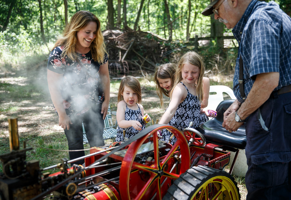 Caroline Wood, 3, center, is surprised as her sisters, Ava Wood, 4, center, and Maggie Wood, 6, right, sound the whistles on a 1/3 scale William Foster & Co steam traction engine, built by Dan Mulderig of Arnold, Mo., right, on display during the Antique Show & Farm Fest at the Historic Marbold Farmstead, Saturday, June 24, 2017, in Greenview, Ill. [Justin L. Fowler/The State Journal-Register]
