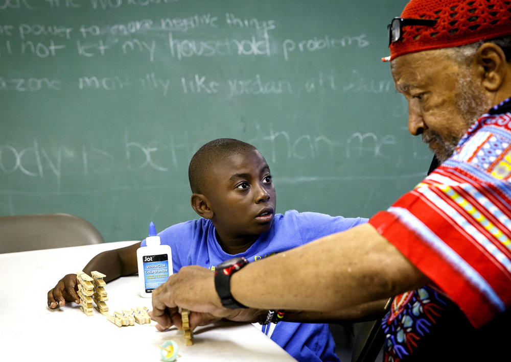 At a summer arts camp in the basement of Calvary Baptist Church, Myondre Anderson, 7, looks to John Crisp, Jr. for help making a craft project Monday, June 19, 2017. City officials have pledged more support for youth programs as an anti-violence measure. The arts camp is organized by the Marcus Garvey Harriet Tubman Cultural Arts and Research Center. [Rich Saal/The State Journal-Register]