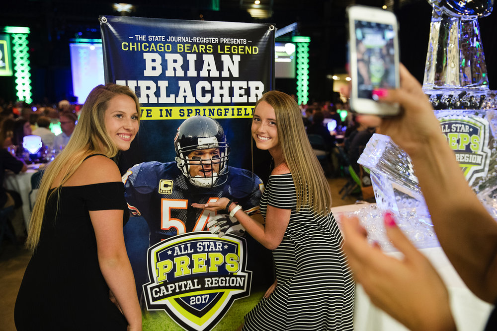Seven Sassano, left and Katie Elmore pose with the poster of former Chicago Bear linebacker Brian Urlacher during The State Journal-Register's inaugural Best of Capital Region Preps awards banquet at the Bank of Springfield Center Tuesday, June 27, 2017.  [Ted Schurter/The State Journal-Register]