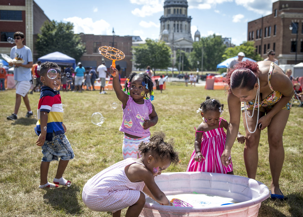 Acelyn Davis, 2, center, launches a cluster of bubbles while playing in one of the several kid stations on the lawn of the former YWCA building during the Jaycees' Capital City Celebration, Saturday, July 1, 2017, in Springfield, Ill. [Justin L. Fowler/The State Journal-Register]