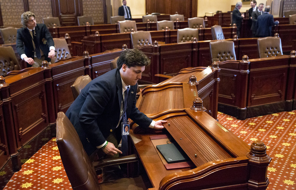 A Senate staff member closes and locks desks after the Senate recessed Tuesday, July 4, 2017 at the Capitol in Springfield, Ill. [Rich Saal/The State Journal-Register]