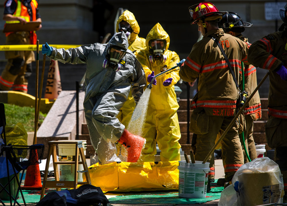 Springfield Firefighter and Hazardous Materials Unit member Phil Peddycoart is rinsed off after investigating a powdery substance thrown in the Governor's office during the overtime session at the Illinois State Capitol, Thursday, July 6, 2017, in Springfield, Ill. [Ted Schurter/The State Journal-Register]