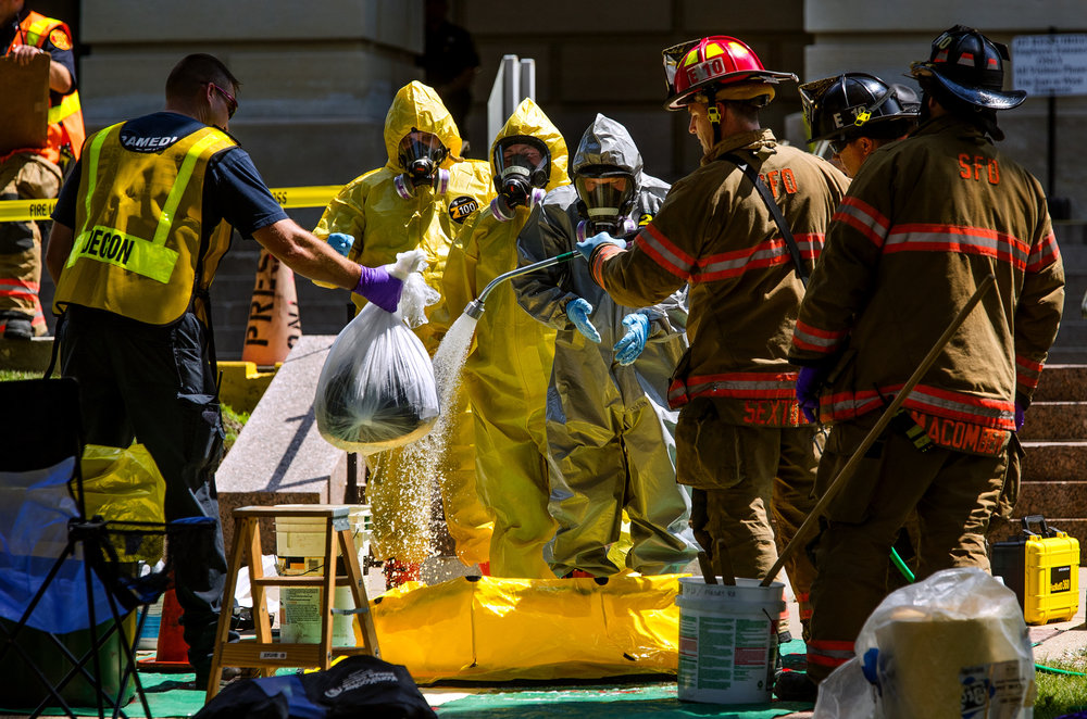 Members of the Springfield Fire Department rinse off items retrieved from inside the Illinois State Capitol by the Hazardous Materials Unit after after a woman threw a powdery substance in the Governor's office during the overtime session at the Illinois State Capitol, Thursday, July 6, 2017, in Springfield, Ill. [Ted Schurter/The State Journal-Register]