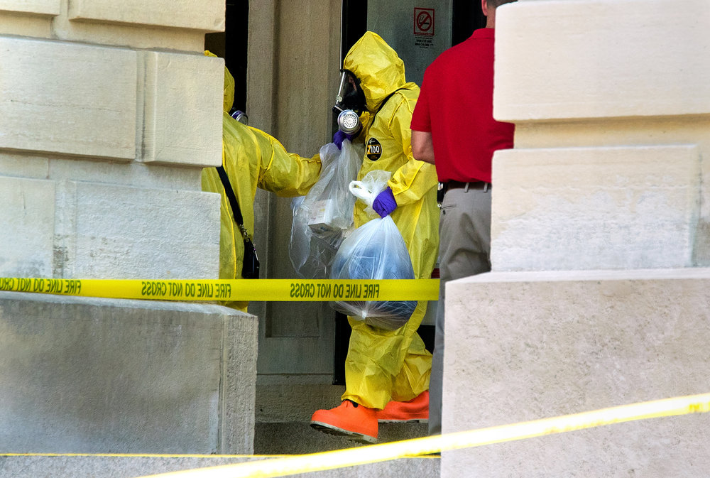 Springfield Firefighter and Hazardous Material Unit member Rick Rojas carries items retrieved from inside the Illinois State Capitol after after a woman threw a powdery substance in the Governor's office during the overtime session at the Illinois State Capitol, Thursday, July 6, 2017, in Springfield, Ill. [Ted Schurter/The State Journal-Register]