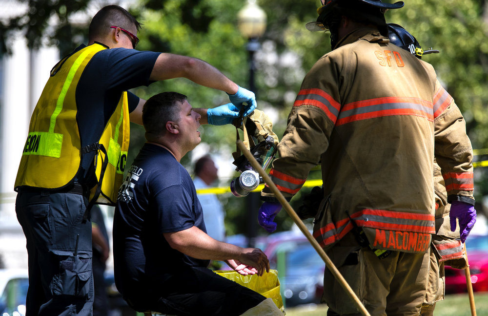 Springfield Firefighter and Hazardous Material Unit member Jonathan Gordon exhales as his mask is removed after he helped investigate a powdery substance thrown in the Governor's office during the overtime session at the Illinois State Capitol, Thursday, July 6, 2017, in Springfield, Ill. [Ted Schurter/The State Journal-Register]