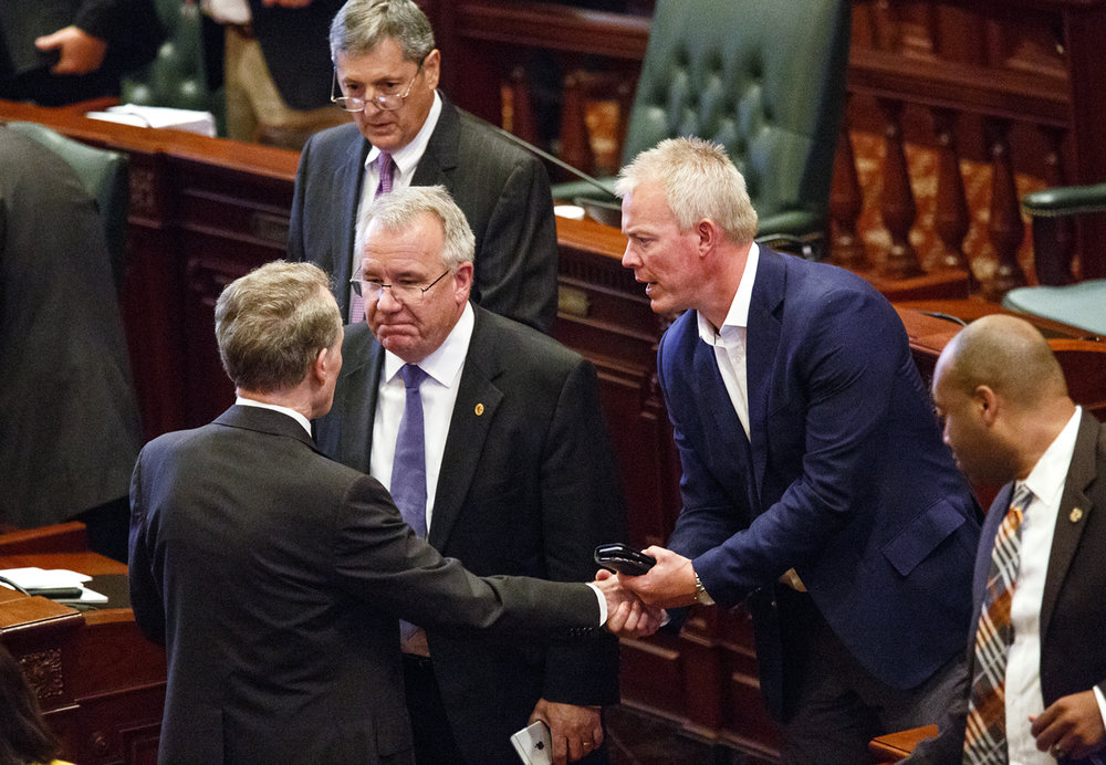 House Speaker Michael Madigan, D-Chicago, left, speaks with Rep. Steven Andersson, R-Geneva, center, and Rep. Brandon Phelps, D-Harrisburg after the House vote to override Gov. Bruce Rauner's veto of a package of budget bills and at the Capitol Thursday, July 6, 2017. Anderson and Rep. David Harris, R-Mount Prospect, behind him,  both voted with Democrats to override the governor's veto. [Rich Saal/The State Journal-Register]