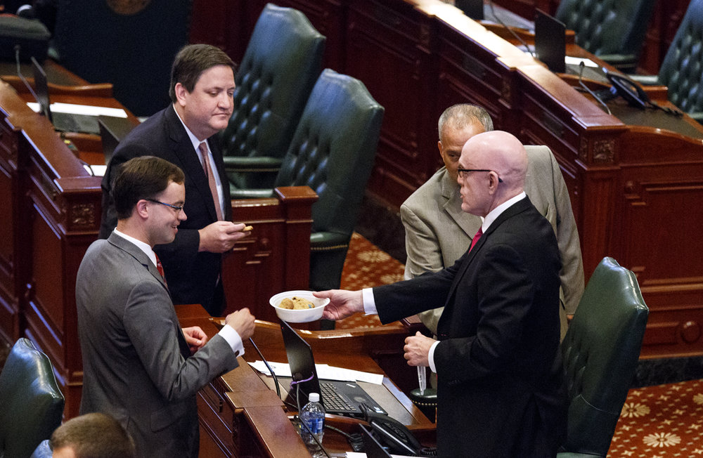 Rep. Greg Harris, D-Chicago, passes out cookies to Rep. David Olsen, R-Downers Grove, left, and Rep. David McSweeney, R-Cary before the start of a special session at the Capitol in Springfield, Ill. Thursday, July 6, 2017.