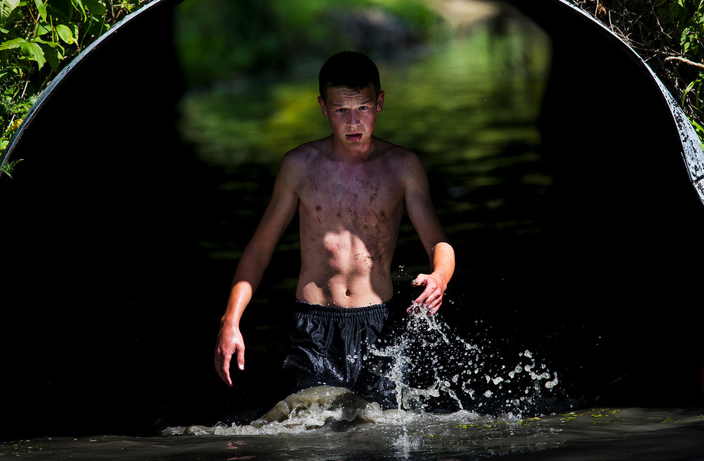 A participant emerges from a watery culvert during the Big Dawg Dare in Litchfield Saturday, July 15, 2017. The race is an extreme 5k featuring muddy bogs, water, uphill climbs and obstacles. [Ted Schurter/The State Journal-Register]