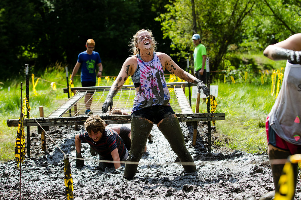 Claire Caldwell pauses and laughs as she tries to navigate the muck during the Big Dawg Dare in Litchfield Saturday, July 15, 2017. The race is an extreme 5k featuring muddy bogs, water, uphill climbs and obstacles. [Ted Schurter/The State Journal-Register]