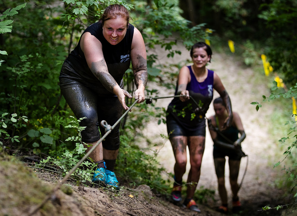 Robin Gilmore leads Melissa Boatman and Alyse Sandino up the big hill climb during the Big Dawg Dare in Litchfield Saturday, July 15, 2017. The race is an extreme 5k featuring muddy bogs, water, uphill climbs and obstacles. [Ted Schurter/The State Journal-Register]