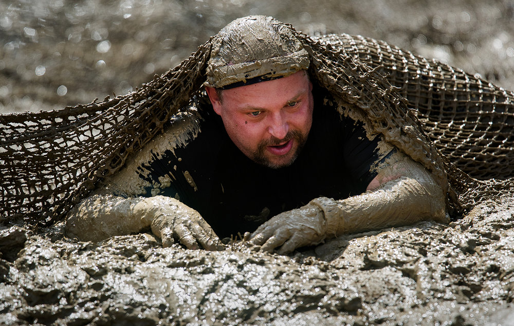 Tom Varner emerges from under a net-covered mug bog near the conclusion of the Big Dawg Dare in Litchfield Saturday, July 15, 2017. The race is an extreme 5k featuring muddy bogs, water, uphill climbs and obstacles. [Ted Schurter/The State Journal-Register]