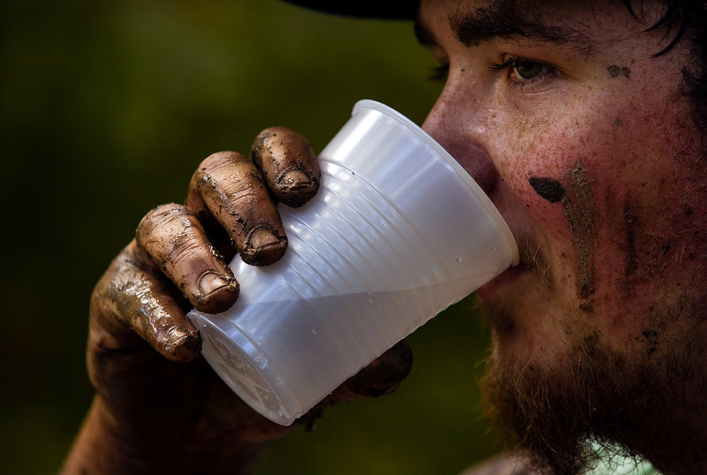 Zach Broschayt pauses for a drink after the big hill climb during the Big Dawg Dare in Litchfield Saturday, July 15, 2017. The race is an extreme 5k featuring muddy bogs, water, uphill climbs and obstacles. [Ted Schurter/The State Journal-Register]