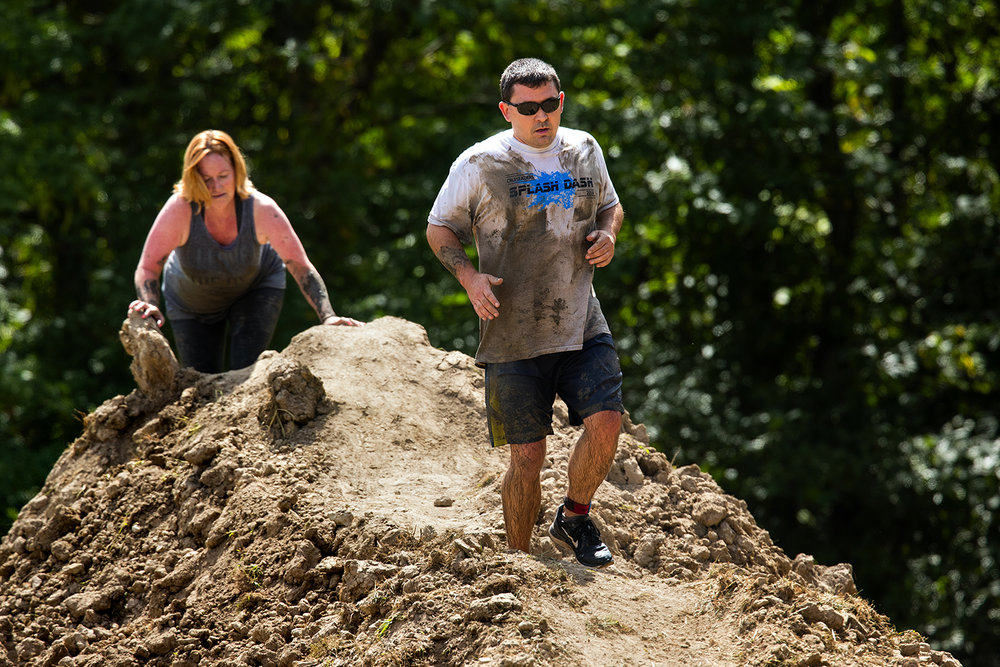 Ed Darabcsek crosses a large dirt pile during the Big Dawg Dare in Litchfield Saturday, July 15, 2017. The race is an extreme 5k featuring muddy bogs, water, uphill climbs and obstacles. [Ted Schurter/The State Journal-Register]