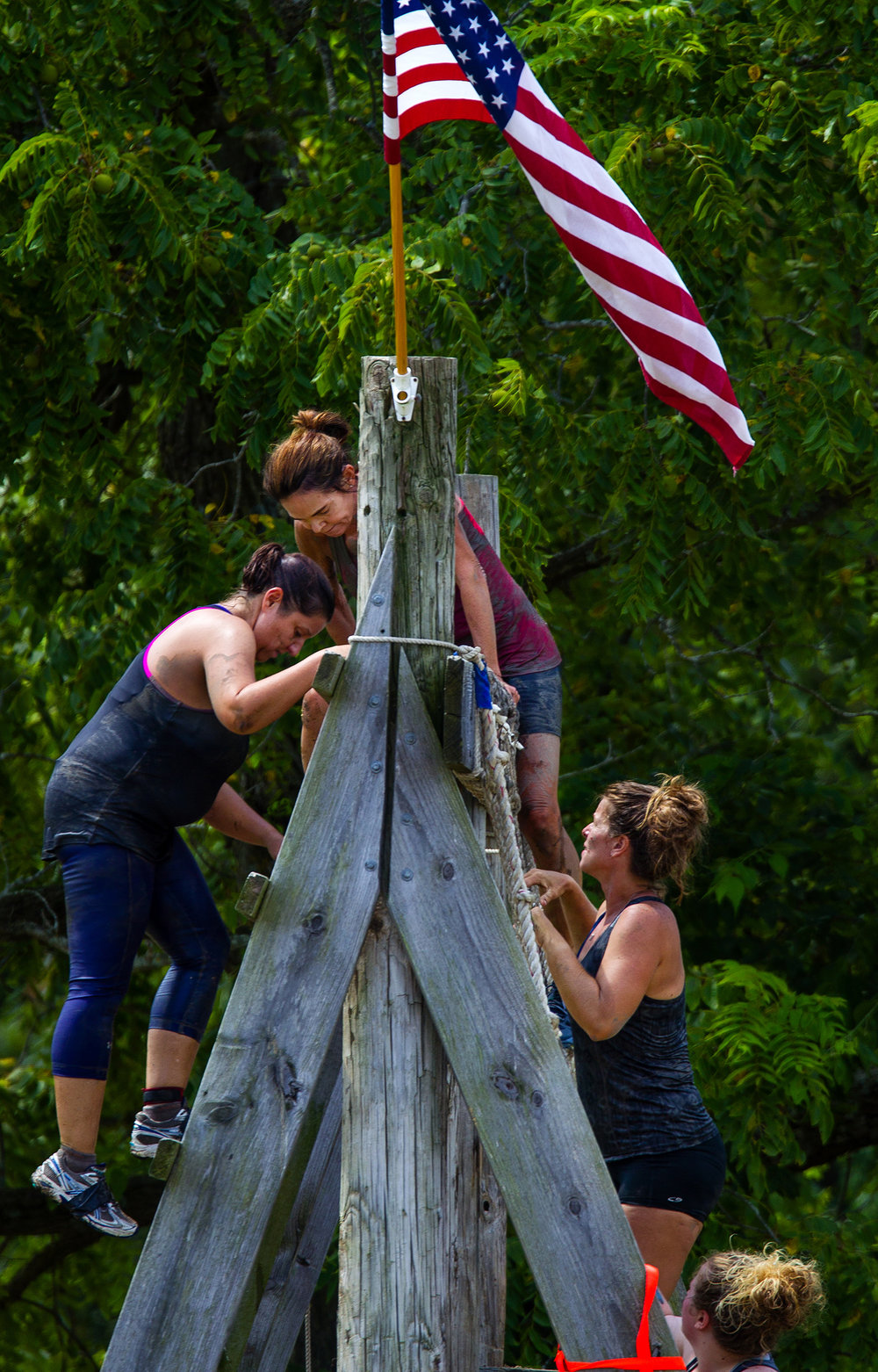 Competitors climb over a large barricade during the Big Dawg Dare in Litchfield Saturday, July 15, 2017. The race is an extreme 5k featuring muddy bogs, water, uphill climbs and obstacles. [Ted Schurter/The State Journal-Register]