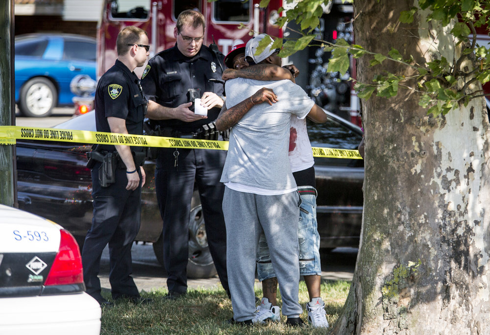 Two men console each other near the scene of shooting where a 26-year-old man was shot multiple times in the parking lot of the West Lake apartment complex in the 100 block of West Lake Shore Drive, Monday, July 10, 2017, in Springfield, Ill. [Justin L. Fowler/The State Journal-Register]