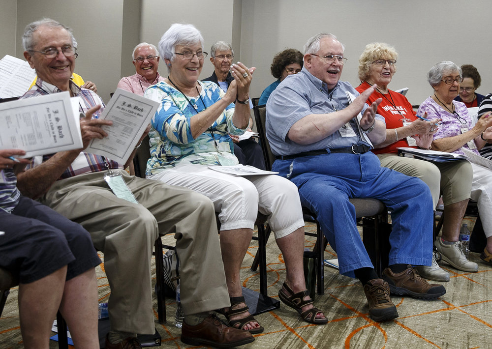"Barb Paul, center, of Frankfort, Ill., joins with her fellow singers as they applaud the piano performance from Karen Ferguson, as the group rehearsed Johann Sebastian Bach's Contatas during rehearsals for the Road Scholar/Elderhostel choral program ""Singing in the Heart of America: A Choral Workshop"" hosted by Lincoln Land Community College at the President Abraham Lincoln DoubleTree hotel, Tuesday, July 11, 2017, in Springfield, Ill. The workshop will include a concert featuring music from various periods on Thursday, July 13, 7 p.m. at St. John's Lutheran Church and is free and open to the public. [Justin L. Fowler/The State Journal-Register]"