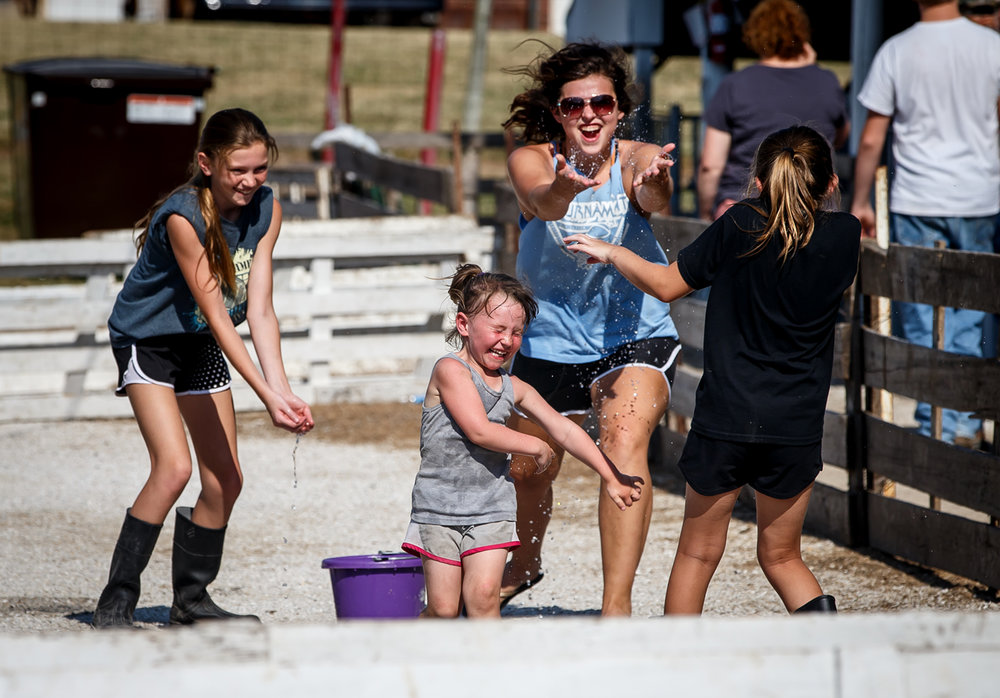 Mekenzie White, 3, center, of Franklin, Ill., tries to escape a water attack from Bell Brown, 12, left, Anita Moore, 18, center, and Reagan Brown, 10, right, all of Winchester, Ill., as they find ways to stay cool outside of the Swine Barns at the Morgan County Fairgrounds, Wednesday, July 12, 2017, in Jacksonville, Ill. Temperatures in the area hit the 90s and the heat index toping 100. [Justin L. Fowler/The State Journal-Register]