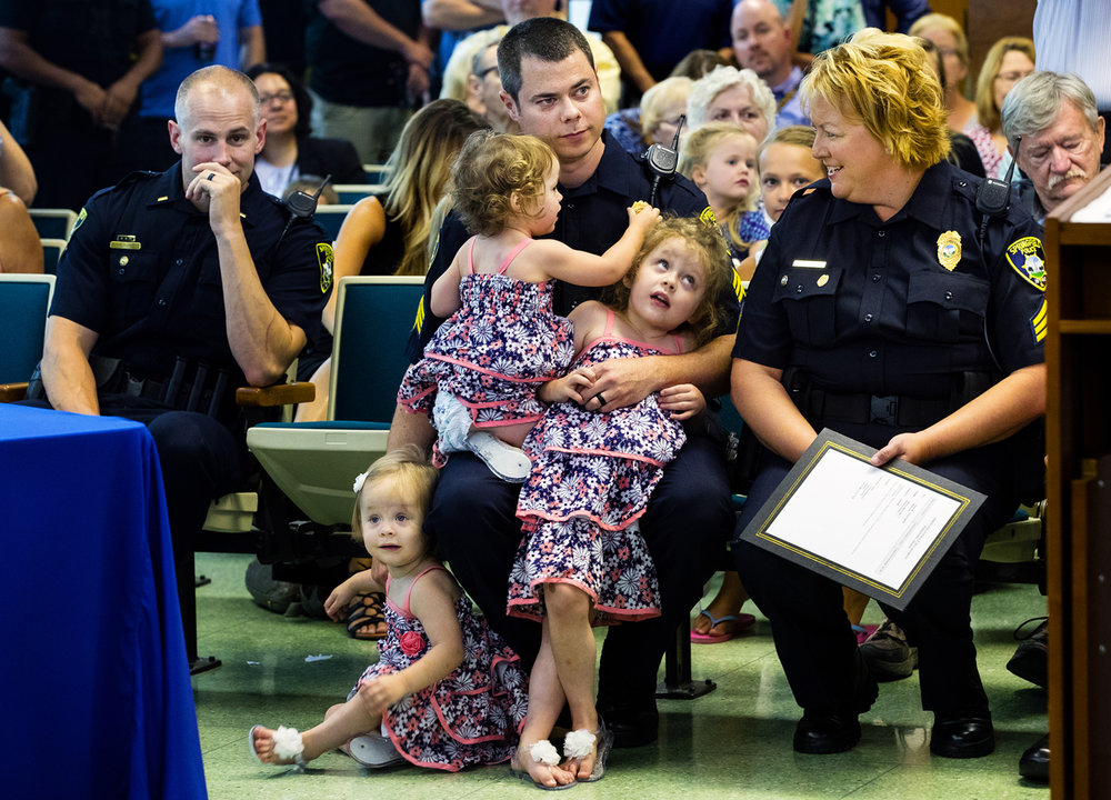 Springfield Police Department Sgt. Tyler Lynn tries to watch promotion ceremonies as he holds his twin daughters Ava, left, and Emma as his daughter Bella glances up at Sgt. Paula Crouch in the City Council chambers Thursday, July 13, 2017. Lynn, who was given permission by Chief Kenny Winslow to pick up his daughter when she began fussing for him, was one of five officers promoted during the ceremony.  Four new officers were also sworn-in. [Ted Schurter/The State Journal-Register]