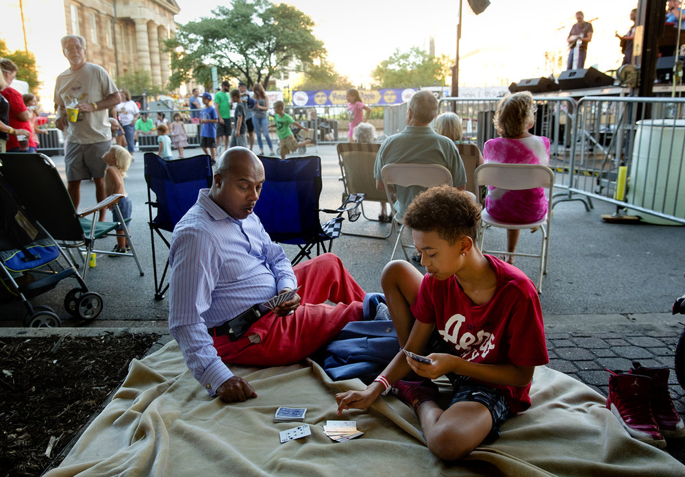 "Bernard Coffey reacts as he plays Gin Rummy with his son Aaron while Amy Benton plays on stage behind them during the ""Amaranth Apple"" Music & Food Fest downtown Friday, July 14, 2017. The festival continues Saturday when gates open at 3 p.m.. [Ted Schurter/The State Journal-Register]"